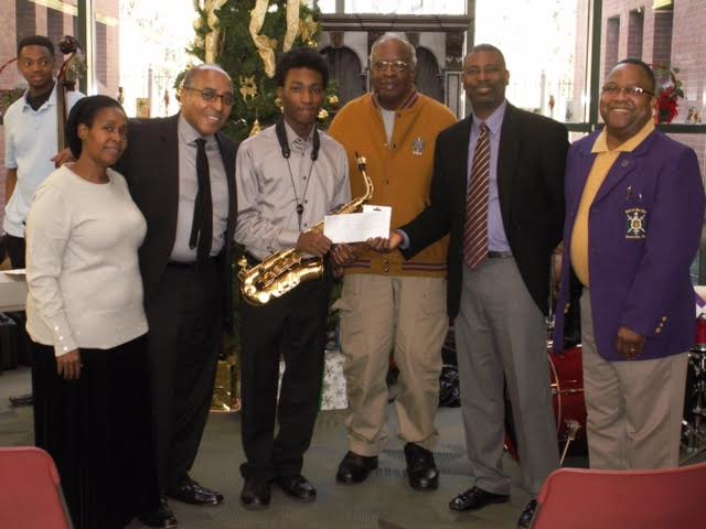 As his parents Mr. John & Rosemary Robertson, proudly look on, Eta Omega's Talent Hunt Winner, James Robertson is presented his award by Basileus Dominic Thurston, Talent Hunt Chairman Ernest Perry, and Bro. Willie Wilkerson