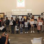 OMLI and ASALH mentees hold up photos of prominent African Americans.